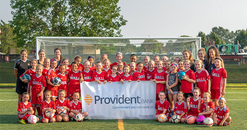 Youth Soccer team holding Provident Banner